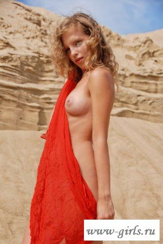 Гимнастка танцует на песке