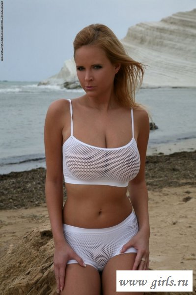 Голая дамочка на пляже у моря и прозрачный бикини