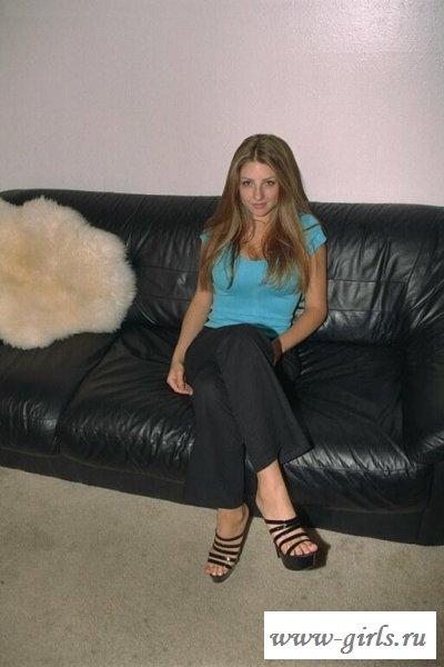 Девушка раздевается на кожаном диване
