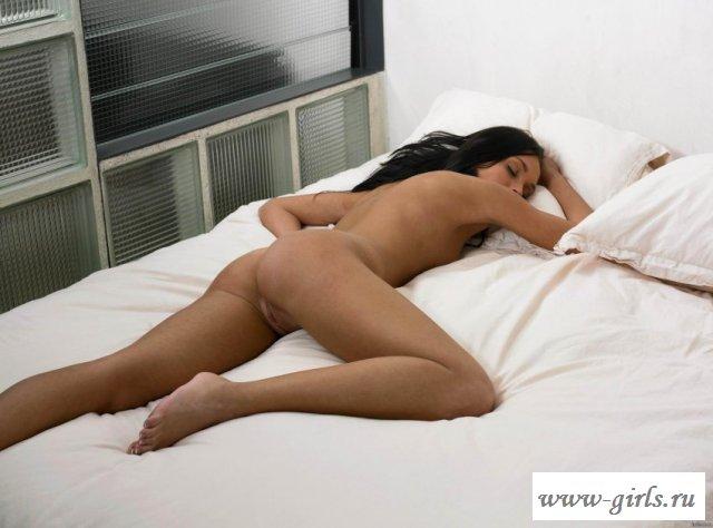 На постели голая девушка со смуглой кожей