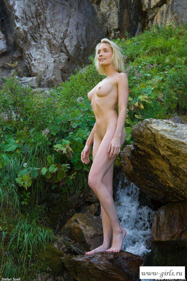 Обнаженная блондинка гуляет по гористой местности