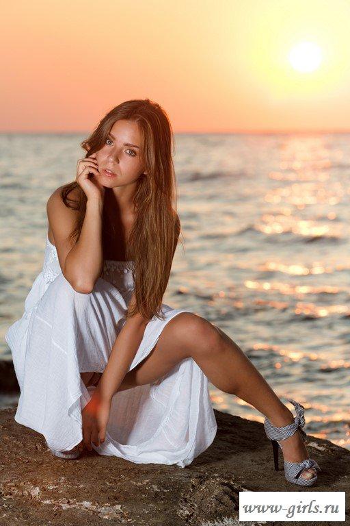 Раздетая красавица с длинными волосами на закате солнца