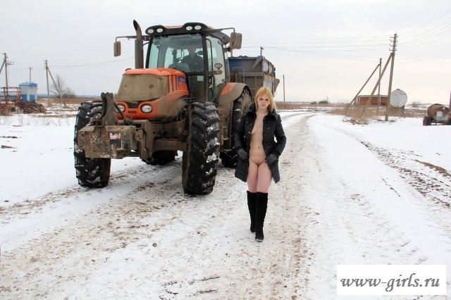 Обнаженная девушка гуляет зимой по деревне