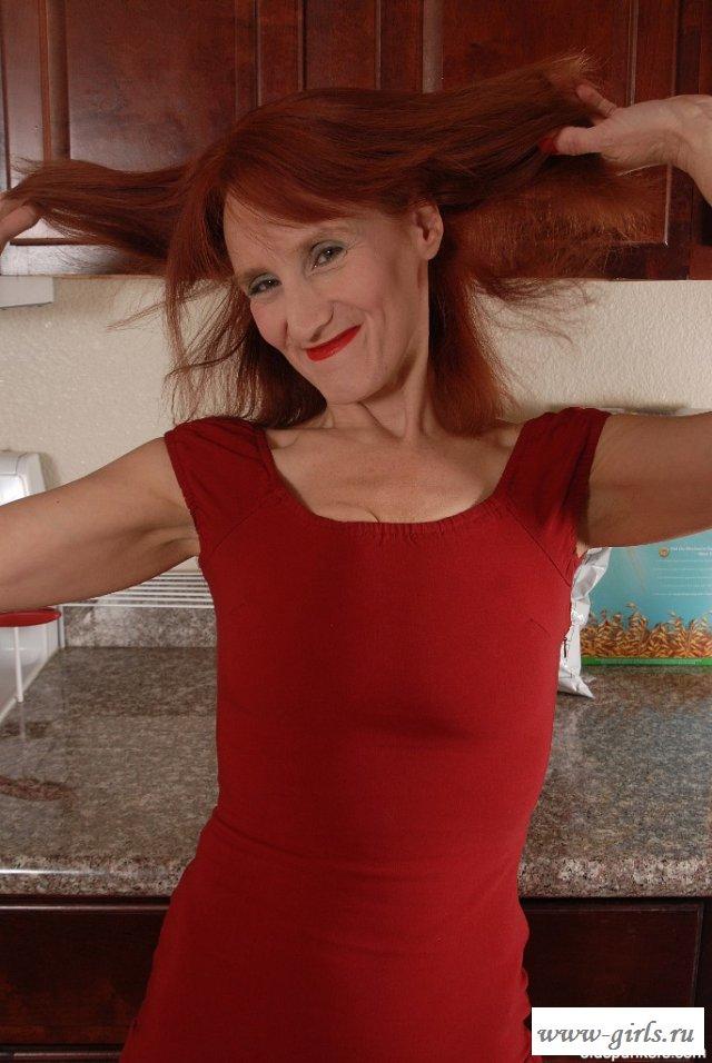 Рыжая женщина на кухне эротично показала сиськи