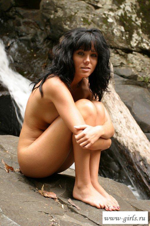 Эротичная брюнетка танцует страстно у водопада